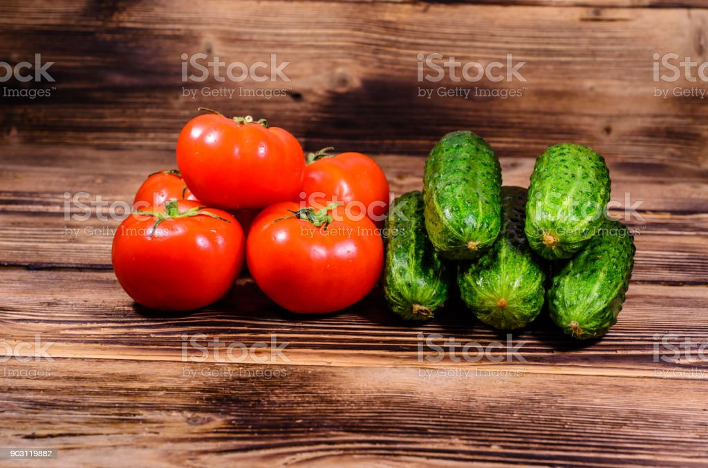 Ripe tomatoes and cucumbers on wooden table stock photo