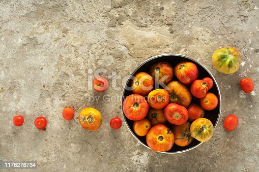 Ripe tomatoes in a bowl on a concrete background