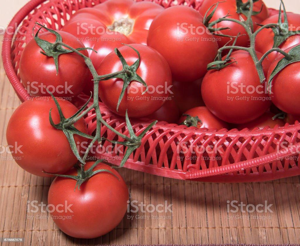 Olgun domates kırmızı sepet içinde. Sepete bırakılan bir piçsin domates demet royalty-free stock photo