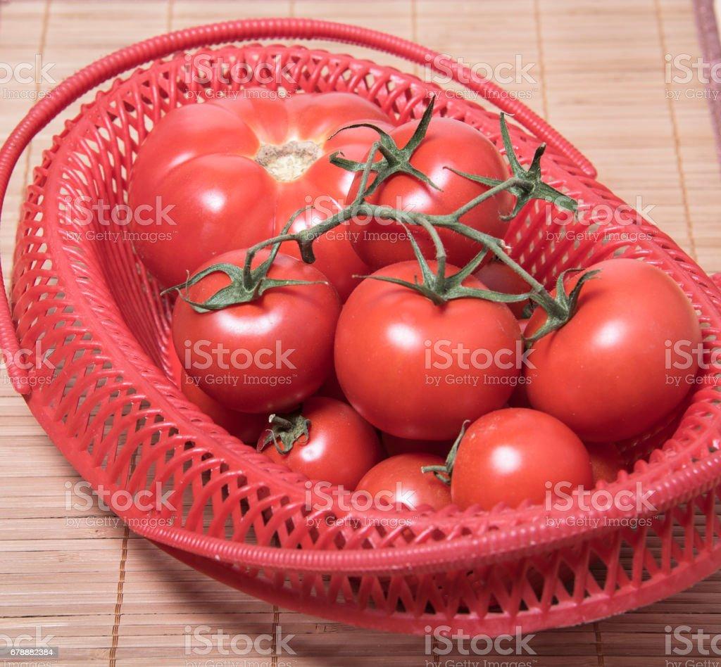 Olgun domates kırmızı sepet içinde. Domates demet royalty-free stock photo