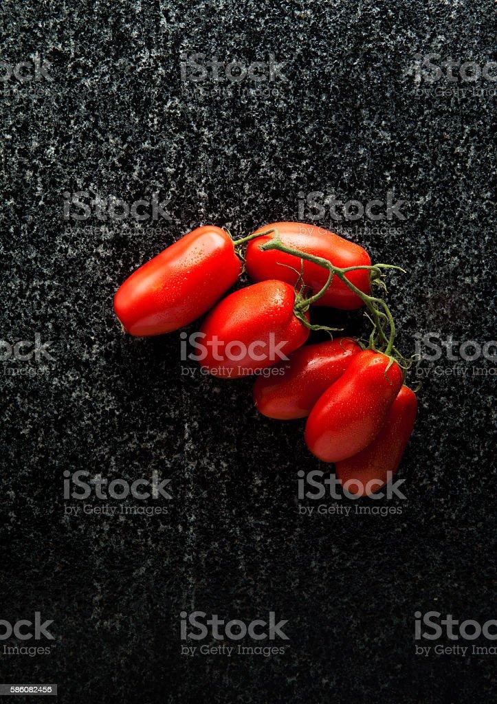ripe tomatoes on black marble stock photo