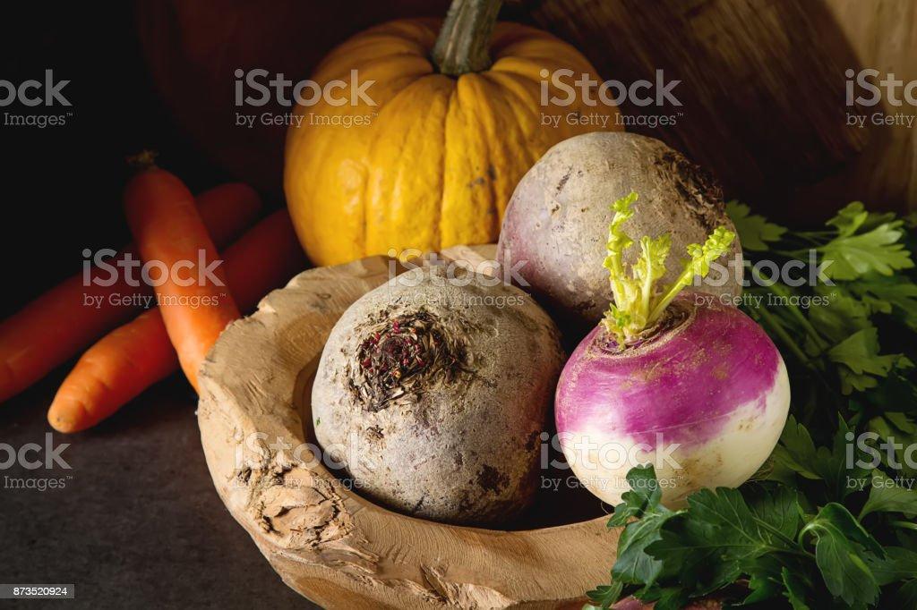Ripe turnips, beets, carrots, pumpkin and parsley. Dark background. Vegetarian food. stock photo