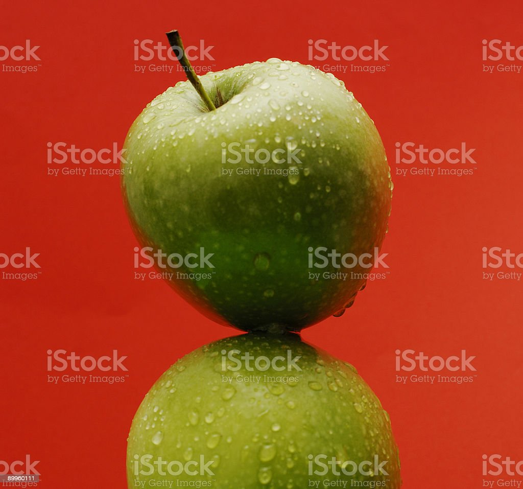 ripe water covered green apple against red royalty-free stock photo