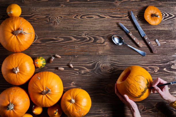 ripe yellow pumpkins over wooden background - human limb stock photos and pictures