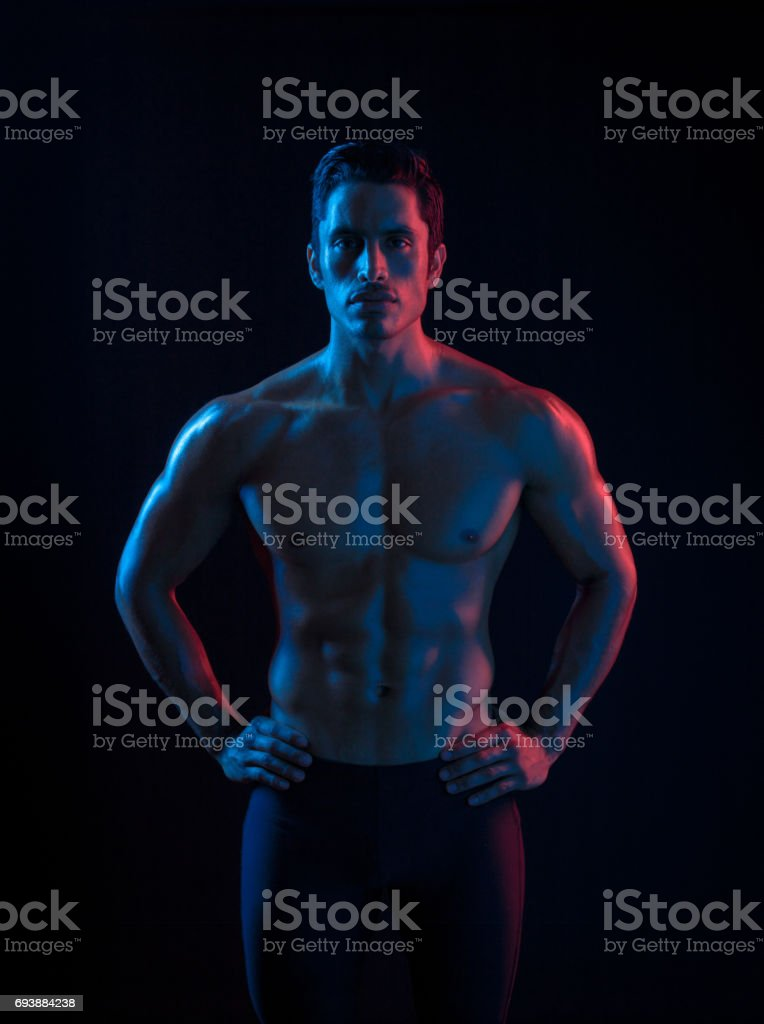 Ripped Hispanic Man In Surreal Colored Lighting stock photo