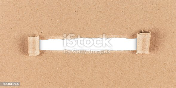 istock ripped hole in brown paper 690503890