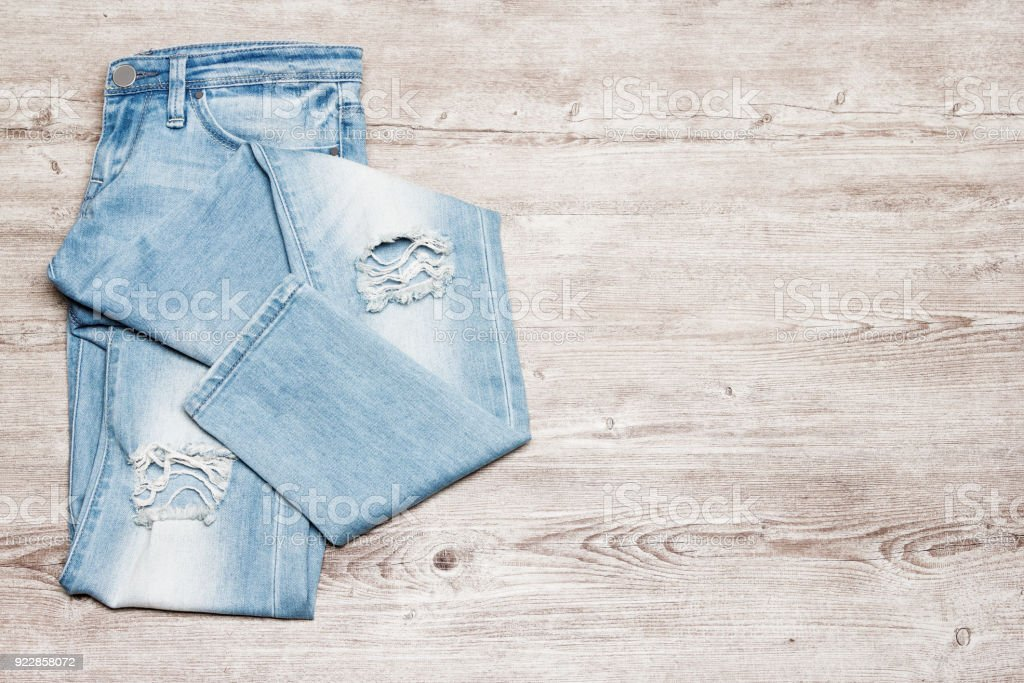 Ripped jeans on shabby wooden background with free space for text stock photo