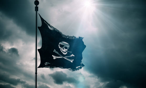 ripped tear grunge old fabric texture of the pirate skull flag waving in wind, calico jack pirate symbol at cloudy sky with sun rays light, dark mystery style, hacker and robber - pirates stock photos and pictures