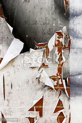 istock Ripped Textured White Paper Posted On Grungy Brick Wall Surface 1171135263
