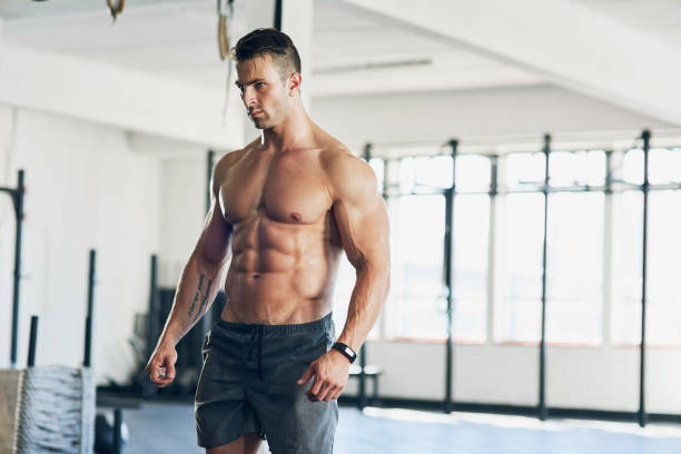 Ripped to perfection Shot of a handsome young man working out at the gym abdominal muscle stock pictures, royalty-free photos & images