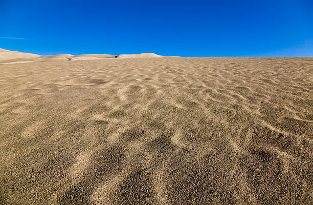 Ripples on sand dunes with blue sky stock photo