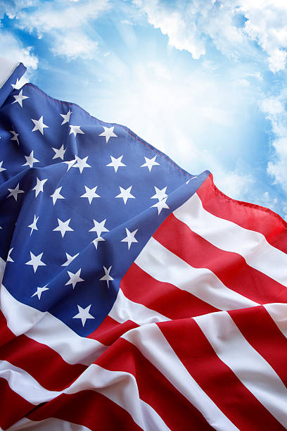 Rippling American flag against blue cloudy sky stock photo