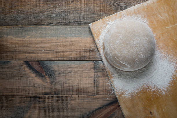 Risen or proofed yeast dough for bread or pizza on a floured slate surface. Top view stock photo