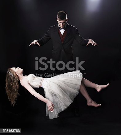 Shot of vaudeville magician levitating a woman on stage