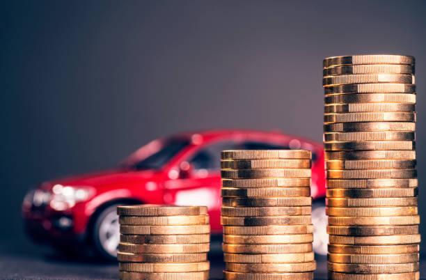 Rising car costs Ansteigende Stapel mit Münzen und einem roten Auto im Hintergrund expense stock pictures, royalty-free photos & images