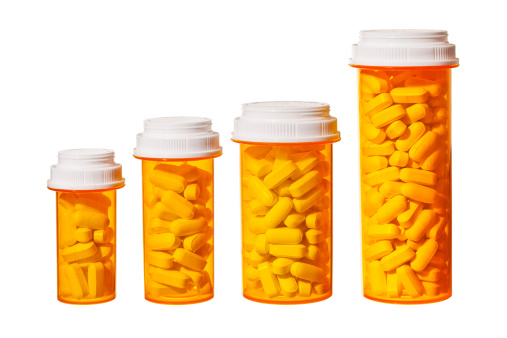 Bottles of pills arranged to represent a bar graph showing the rising cost of medicine and health care.