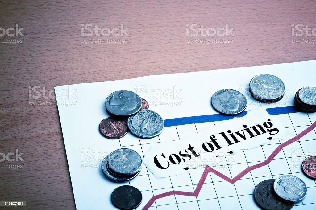 Rising cost-of-living graph with American coins stock photo