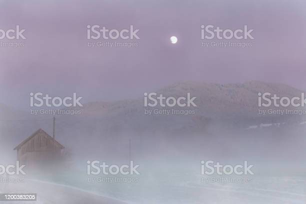 Photo of Rising fog in a moorland with a full moon in autumn