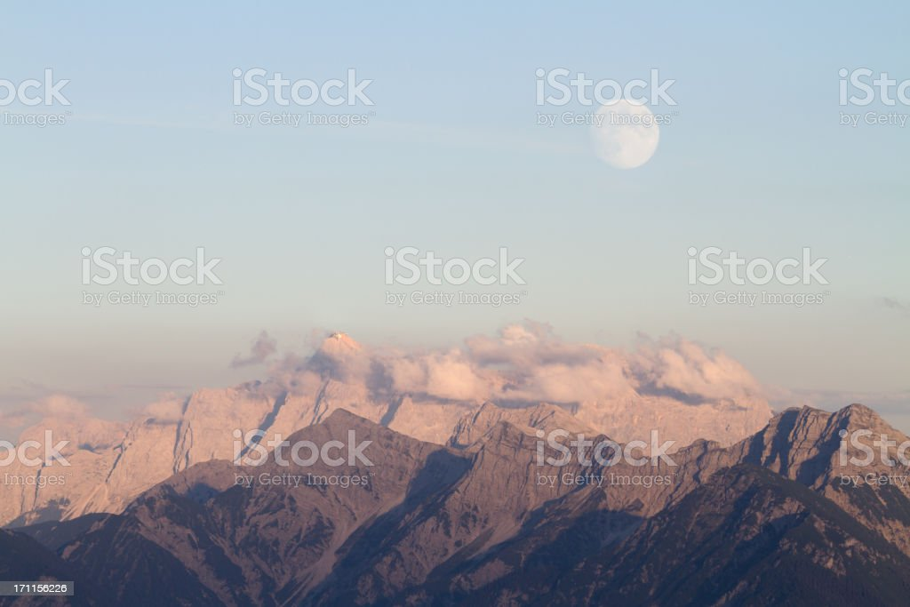 rising full moon over mountains stock photo