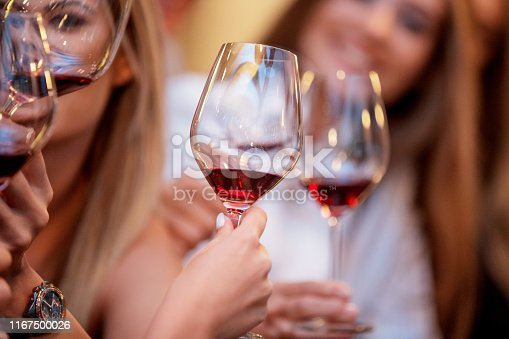 Hands rising glasses of red wine in a celebratory toast