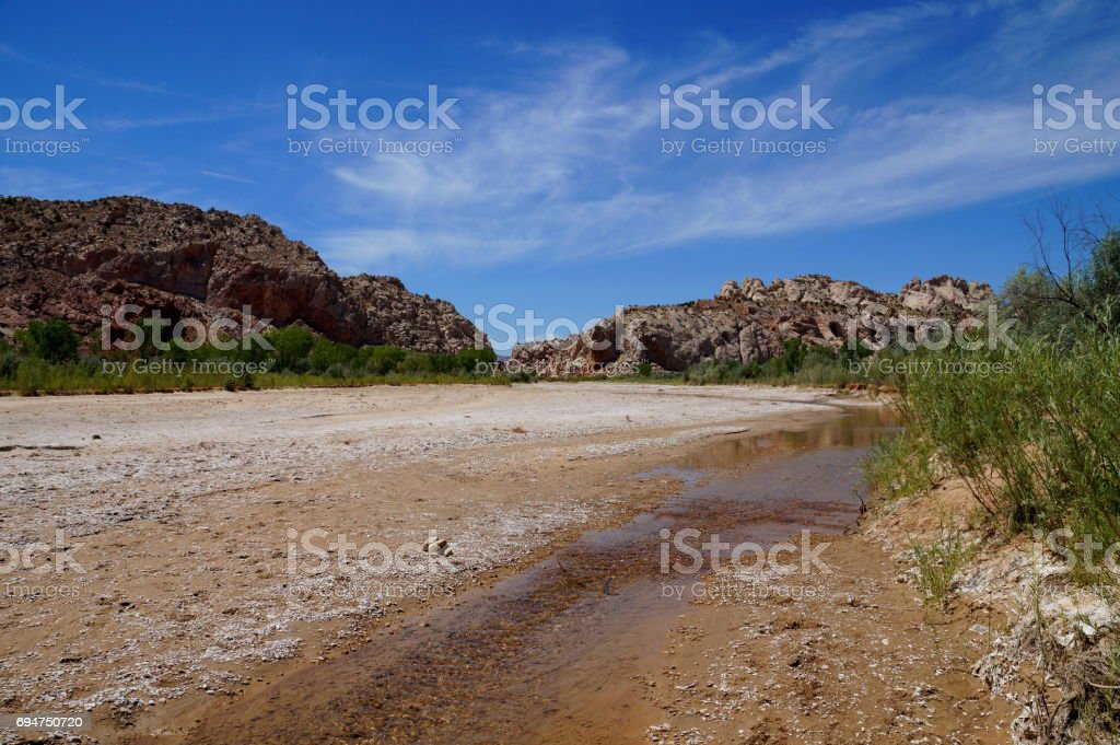Rising global warming: wide river dried out to a tiny stream riverbed stock photo