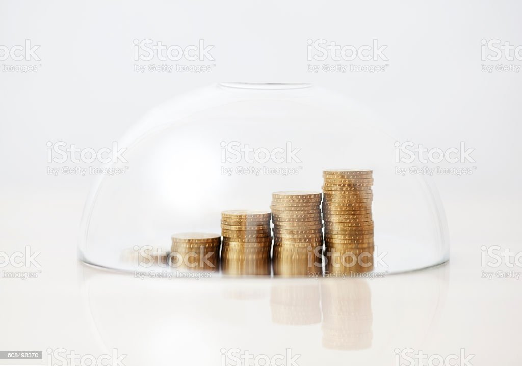 Rising golden coins protected under a glass dome stock photo