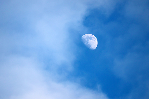 Rising moon in blue sky with white clouds