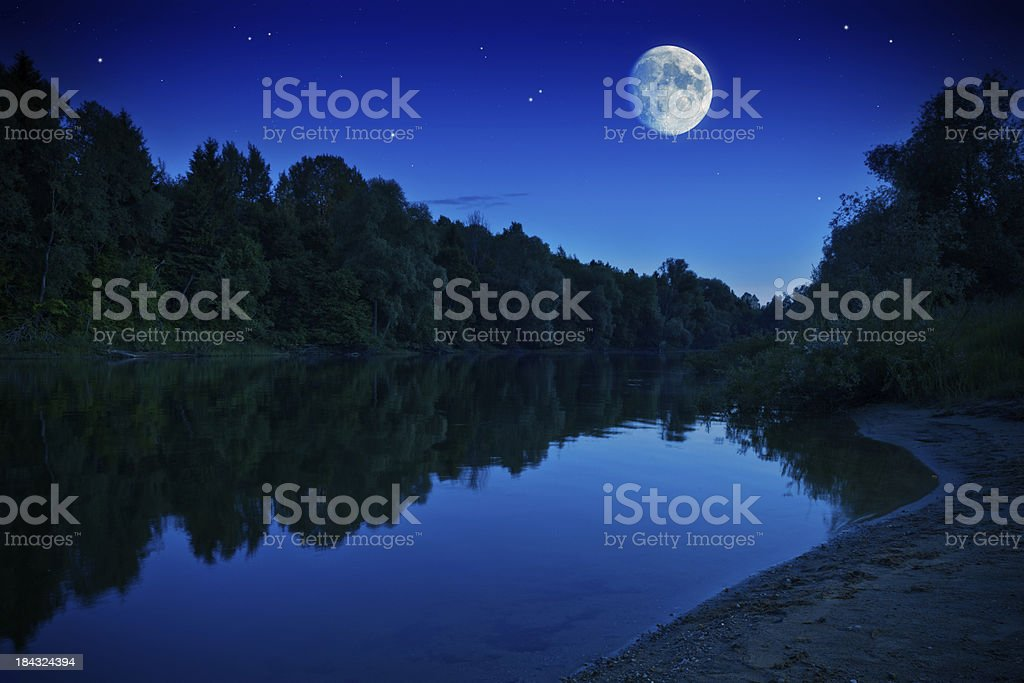 Rising moon over forest river royalty-free stock photo