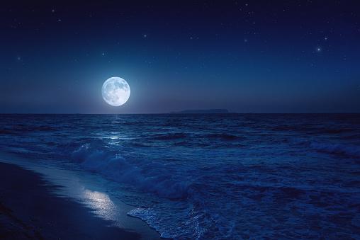 Rising moon over sea. Stock photo.