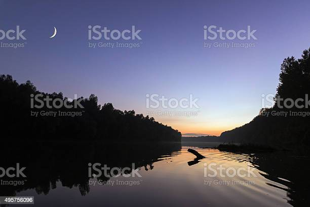 Photo of Rising new moon at sunset, over river.