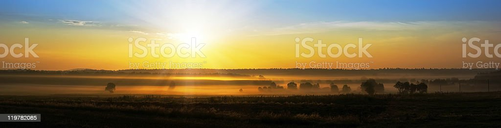 rising sun above the foggy field royalty-free stock photo