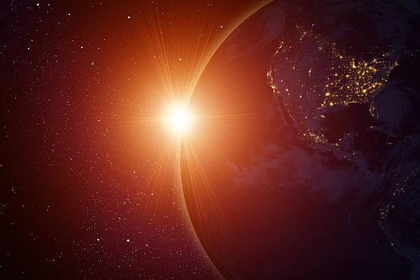 Rising sun behind planet stock photo