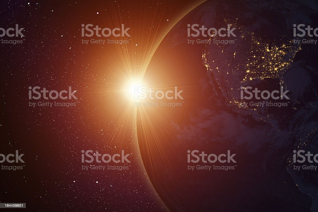 Rising sun behind planet stock photo