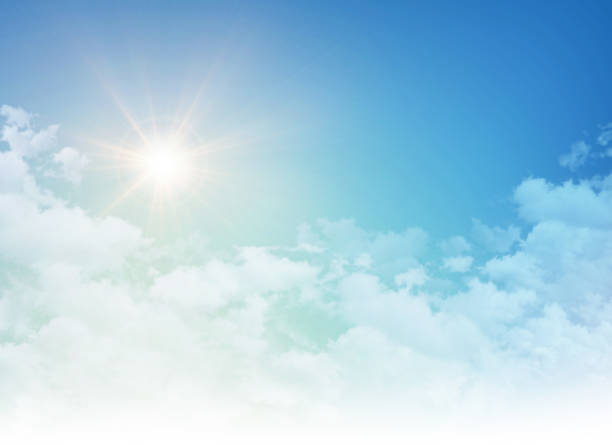 Rising sun in a cloudy blue sky stock photo
