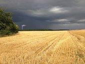Sonne auf Stppelfeld, in der Ferne braut sich ein Gewitter zusammen