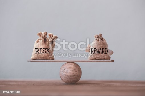 Risk and reward bags on a basic balance scale in equal position on wood table. risk management concept, depicts investors use a risk-reward ratio to compare the expected return of an investment