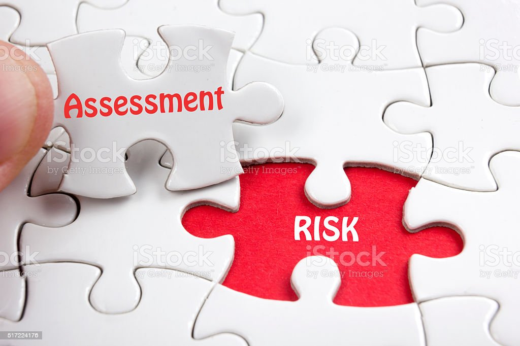 Risk Assessment. Missing jigsaw puzzle pieces with text stock photo