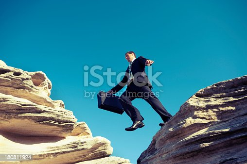 istock Risk concept. Businessman jumping across a ravine. 180811924