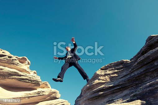 istock Risk concept. Businessman jumping across a ravine. 181897572