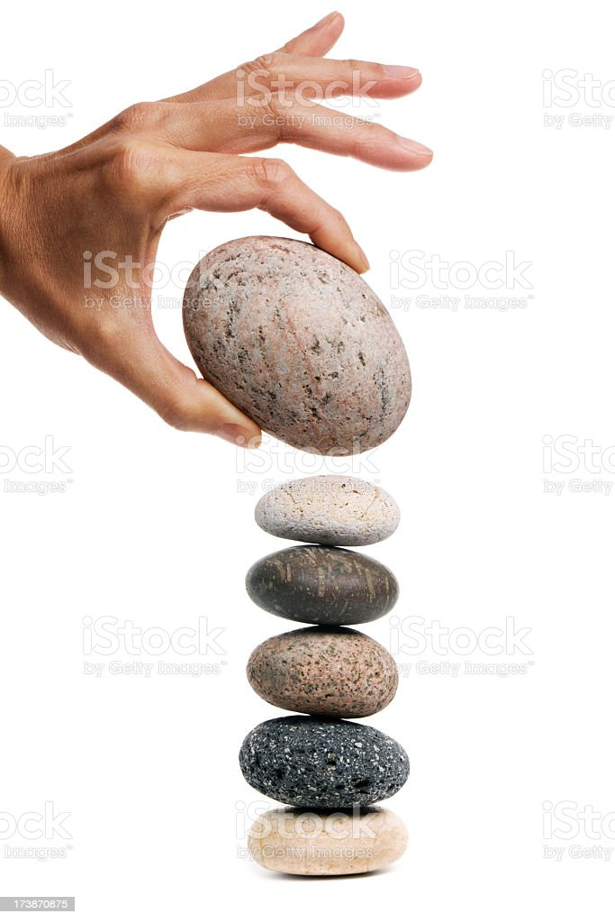 Risk, Danger of Hand Balancing Large Rock on Stone Stack stock photo