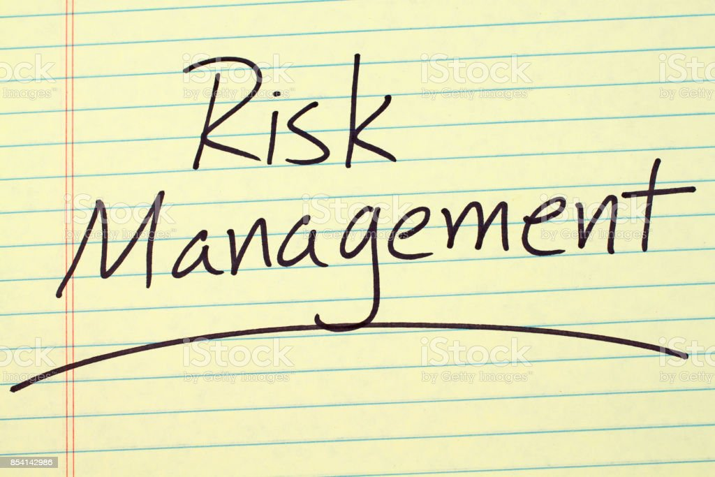 The word \'Risk Management\' underlined on a yellow legal pad
