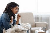 istock Risk Of Coronavirus. Sick Black Woman Coughing Hard At Home 1227312292