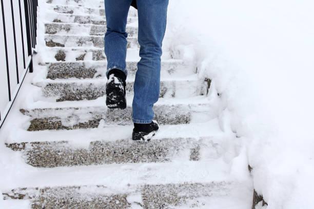 rutschgefahr beim treppensteigen im winter - kaltes wetter stock-fotos und bilder