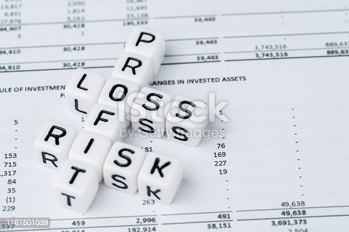 Risk, profit and loss in investment concept, small white cube block with alphabet building the crossword word mainly as Profit with the word Loss and Risk on financial investment reports.
