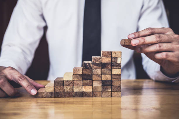 risk to make business growth concept with wooden blocks, hand of man has piling up and stacking a wooden block, alternative risk concept, plan and strategy in business - stability stock photos and pictures