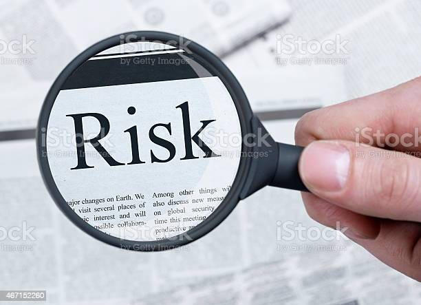 Risk Under Magnifying Glass Stock Photo - Download Image Now
