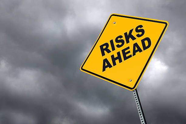 Risks ahead road sign in front of cloudy sky background stock photo