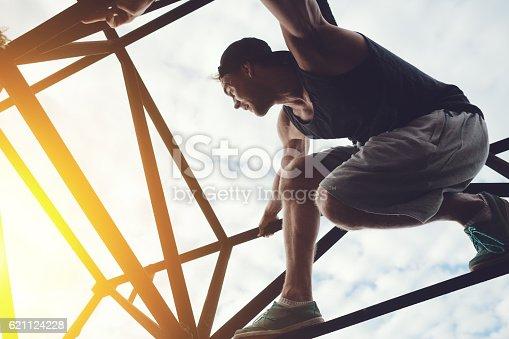 istock Risky man sitting on top of high metal bridge 621124228
