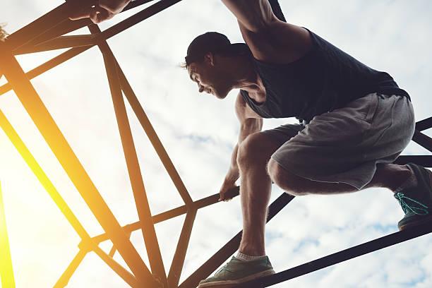 Risky man sitting on top of high metal bridge stock photo