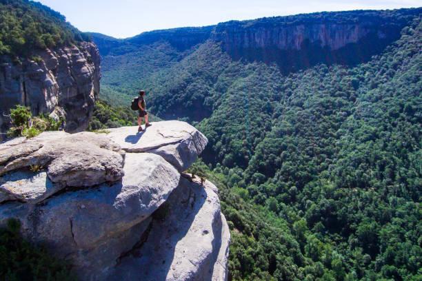 riskante bergsteiger auf einer klippe, blick auf den horizont. - neue abenteuer stock-fotos und bilder